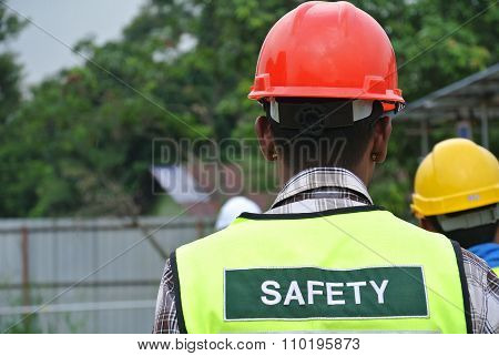 Construction workers wear safety vest has safety sign on it.
