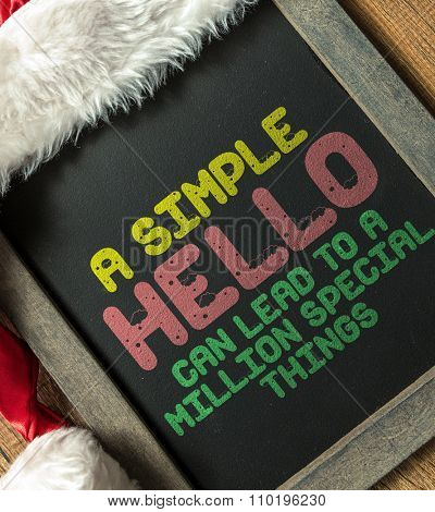 A Simple Hello Can Lead to a Million Special Things written on blackboard with santa hat
