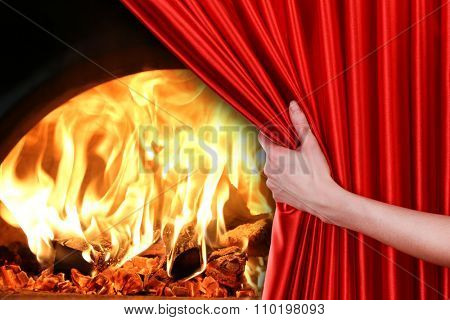 Human hand opens red curtain on fire background