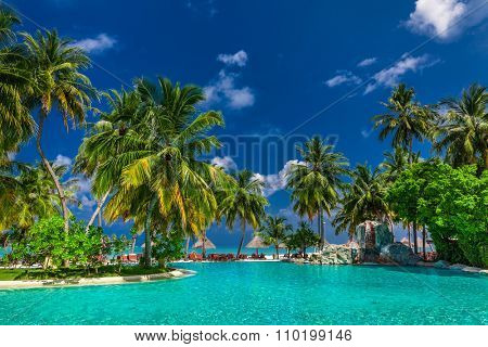 Large infinity swimming pool on the tropical beach with palm trees and umbrellas