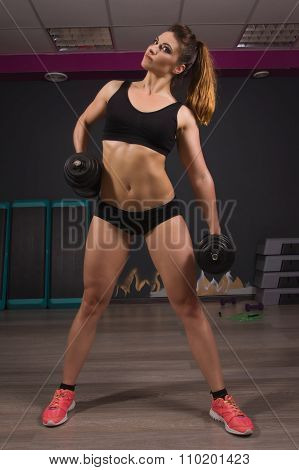 Fit Girl Doing Exercises With Dumbells In Gym