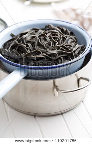 cooked black noodles with squid sepia ink in colander