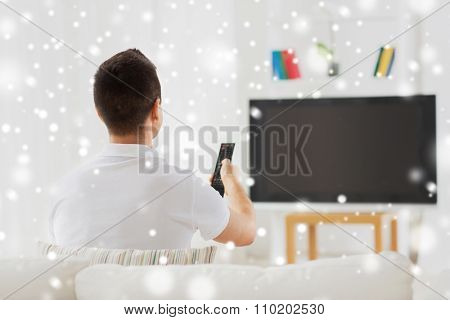 leisure, technology, mass media and people concept - man watching tv and changing channels at home from back over snow effect