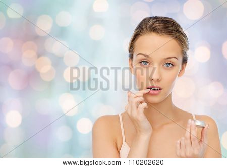 beauty, people and lip care concept - young woman applying lip balm to her lips over blue holidays lights background