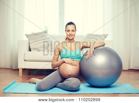 pregnancy, sport, fitness, people and healthy lifestyle concept - happy pregnant woman exercising with fitball at home