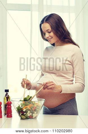 pregnancy, cooking food, healthy lifestyle, people and expectation concept - happy pregnant woman mixing vegetable salad in bowl at home