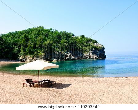 Vacation Concept. Two Chairs Under A White Umbrella On A Sandy Beach In Sheltered Bay. Mediterranean