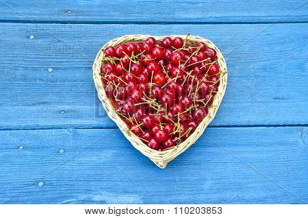 Heart Shaped Wicker Basket Full Of Cherries On Blue Background
