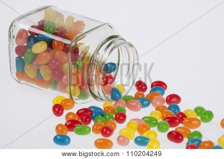 Jelly Beans Candy Spilled From Glass Jar Isolated On White Background