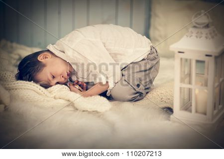 Cute child relaxed on warm woolen plaid at home