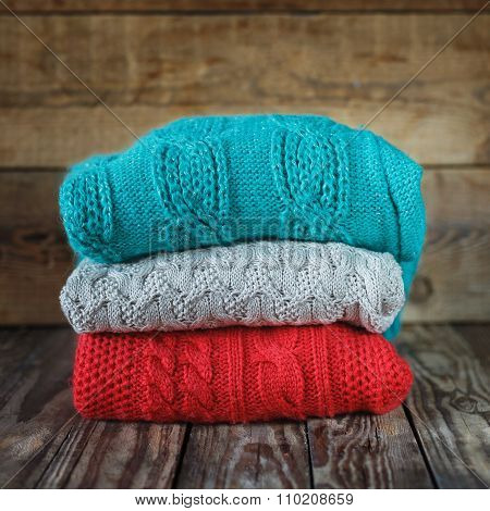 Stack Of Colorful Knitted Sweaters On Wooden Background.square