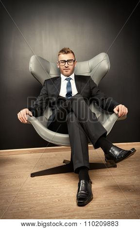Imposing mature man in elegant suit sitting on a leather chair in a modern luxurious interior. Fashion. Business.