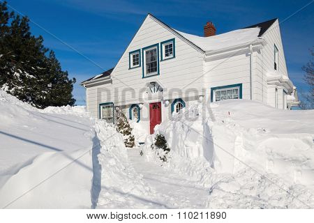 Traditional family home in a north American suburb buried with snow.