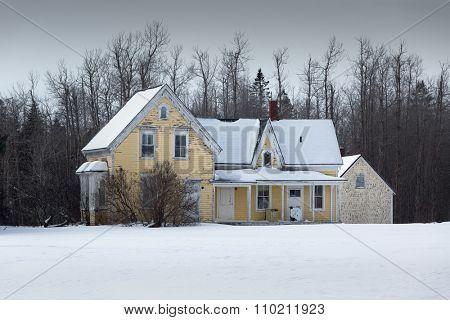 An abandoned farmhouse after a snow fall.