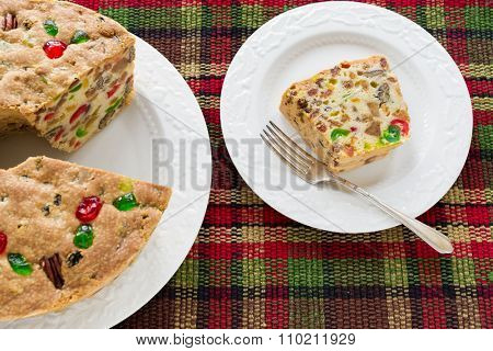 A homemade light Christmas fruitcake on a plaid tablecloth.