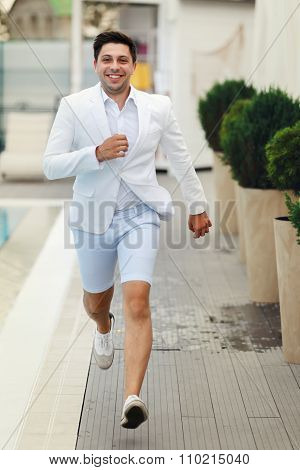 Handsome Confident Groom In White Suit Running Near Pool At Resort