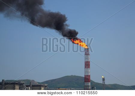 Torch Of Burning Accompanying Gas From Refinery Stack Against Blue Sky