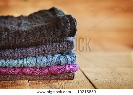 Stack Of Knitting Colorful  Warm Woolen Clothes On Wooden Wall B