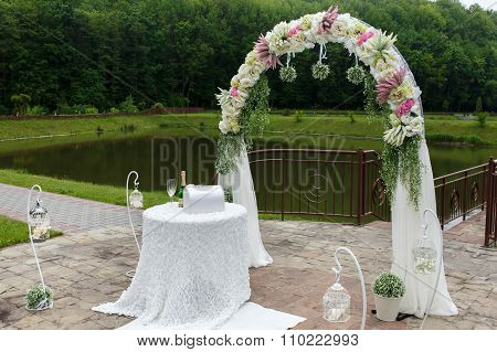 Vintage Stylish Wedding Aisle With A White Floral Arch, A Lake And A Forest In The Background