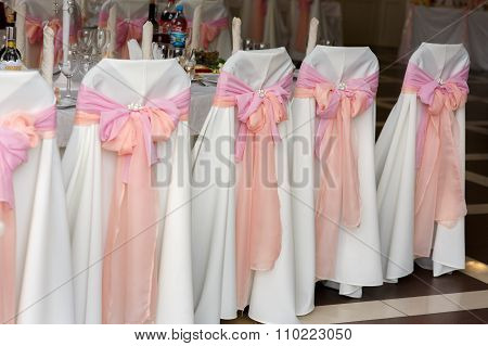 Beautiful Decorated White Wedding Chairs With Pink And Orange Ribbons In Venue