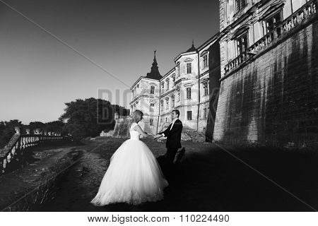 Black And White Elegant Bride In White Dress And Groom In Suit Dancing Near An Old Castle