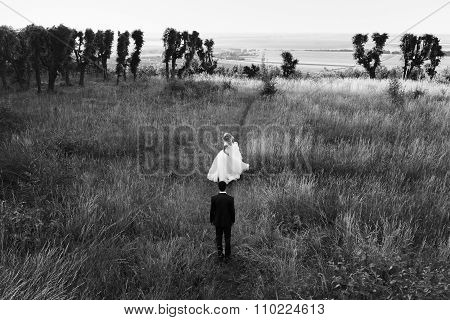 B&w Happy Young Stylish Bride And Handsome Groom Walking In The Field