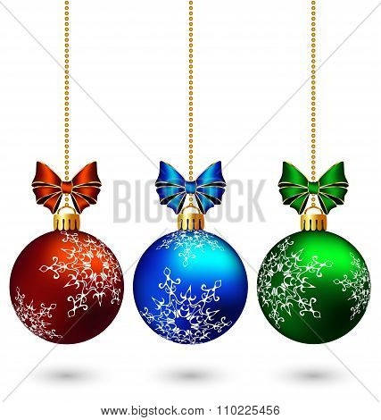Three multicolored christmas balls with bows isolated on white