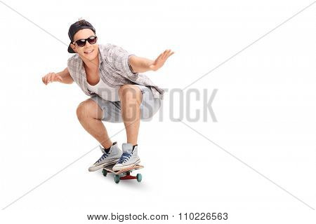 Studio shot of a young joyful skater riding a skateboard isolated on white background