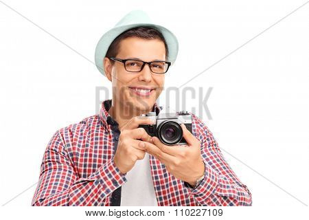 Studio shot of a male photographer holding a camera and posing isolated on white background
