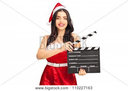 Young woman in Santa costume holding a movie clapperboard and looking at the camera isolated on white background