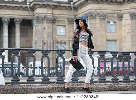 Full length portrait of stylish and beautiful girl posing on the background of old city buildings