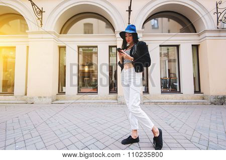 Young woman dressed in trendy clothes using cell telephone during walking in city