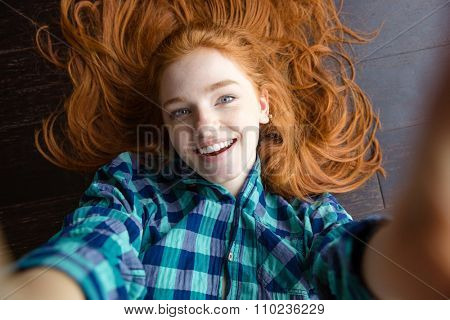 Close up portrait of cheerful beautiful redhead young woman in plaid shirt making self image lying on the floor