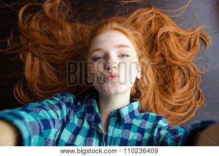 Top view of attractive playful young woman with beautiful red hair in checkered shirt making selfie and sending air kiss lying on the floor