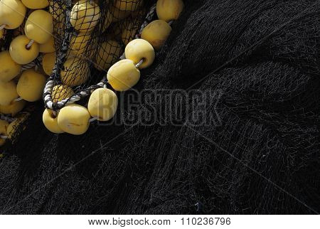 Closeup Of Black Fishing Net With Yellow Floats