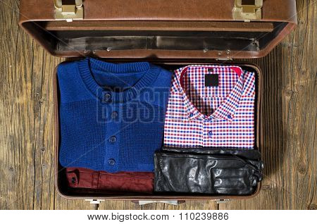 Open travel suitcase with casual man clothes. Top view