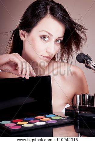 Seductive Woman With Cosmetics For Makeup.