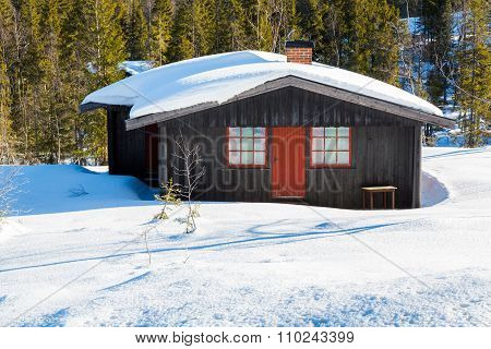 Typical Black Norwegian Cabin Covered In Snow In The Forest