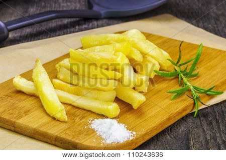 Frensh fries with rosemary on table