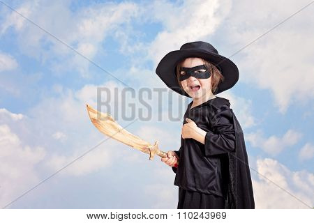 Superhero Child With Sward And Costume On A Blue Sky Background