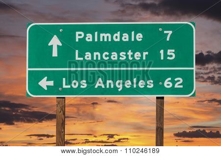 Palmdale, Lancaster and Los Angeles highway sign with sunset sky.