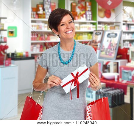 Smiling woman with envelope over shopping mall background.