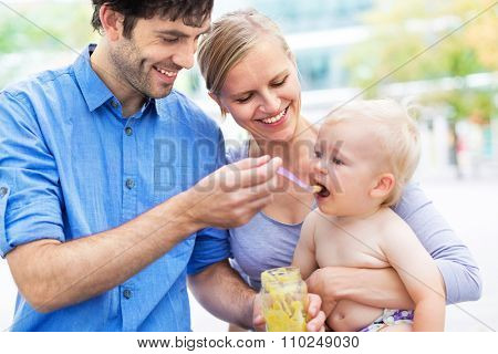 Parents feeding baby by spoon