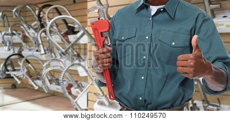Plumber hands with a pipe wrench over plumbing tools background.