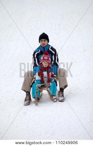 Boy With Dad, Sitting On A Sledge, Going Down On The Hill