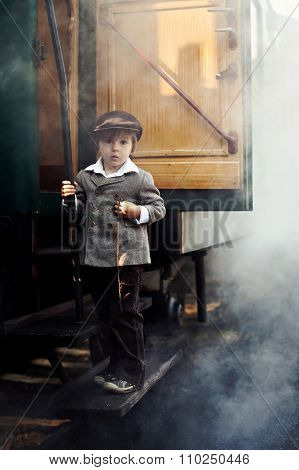 Boy, Dressed In Vintage Coat And Hat, Standing On Stairs Of Steam Train