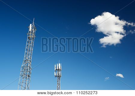 Telecommunications towers with clear blue sky and cloud.