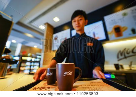 SHENZHEN, CHINA - OCTOBER 22, 2015: cup with hot coffee on the tray in McCafe's. McCafe is a coffee house style food and drink chain, owned by McDonald's.