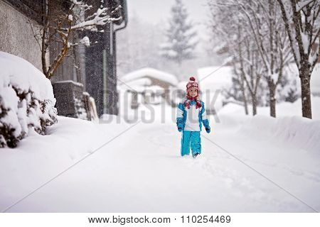 Little Boy In A Snowsuit Walking Through A Snowy Path With Deep Snow Banks On Either Side