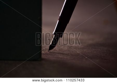 Classy pen lying on a book against a black background